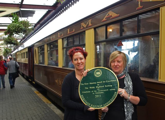 Pont Croesor Station Mistress Belinda Gammon and F&WHR Volunteer Coordinator Tricia Doyle with the HRA Award alongside a WHR train at Porthmadog Harbour Station